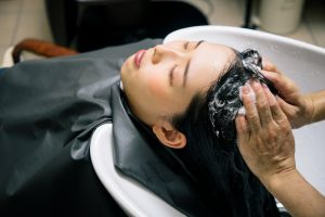 woman getting her hair washed in a shampoo bowl at a salon