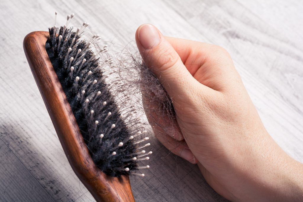 someone cleaning hair out of a boar bristle hair brush