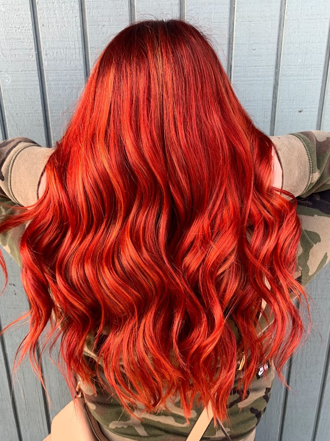 A woman with bright red hair after getting a fashion hair color at Mill Pond Salon.