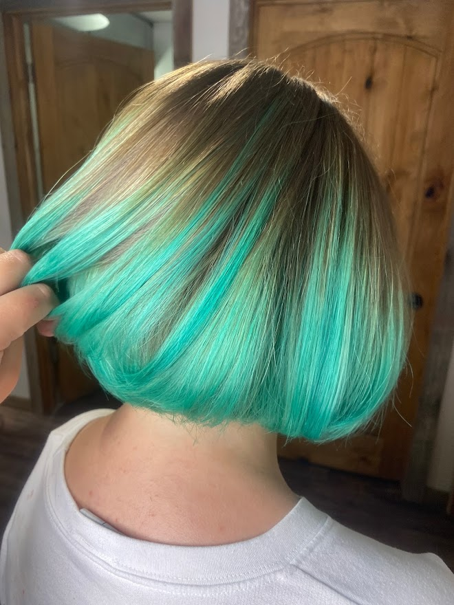 A bright turquoise fashion color on a blonde bob hair cut.