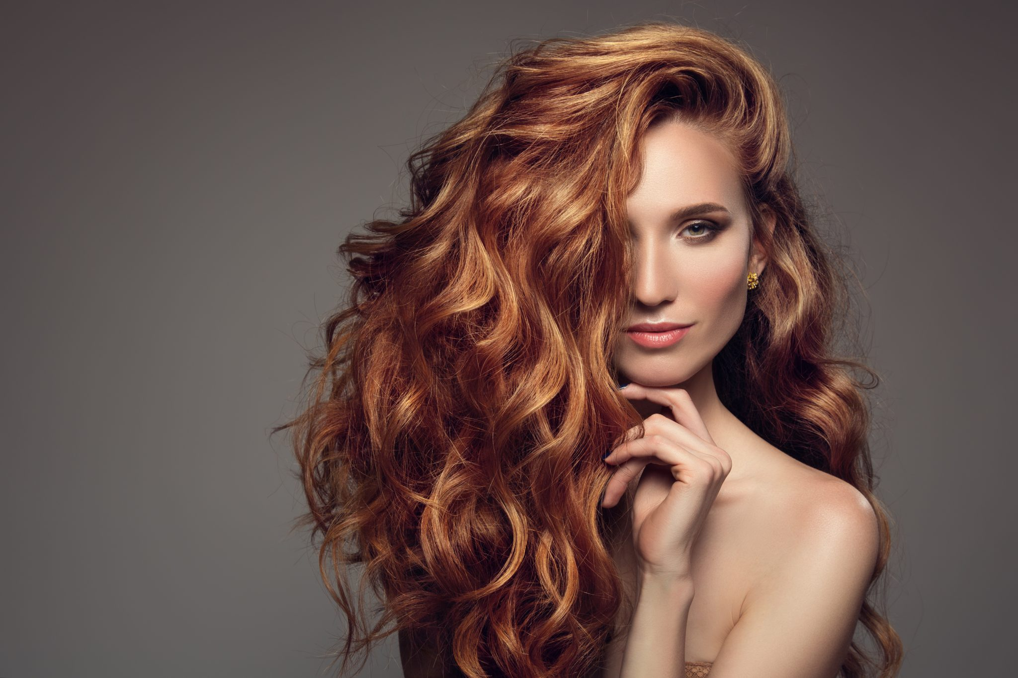 Portrait of woman with long curly beautiful ginger hair.