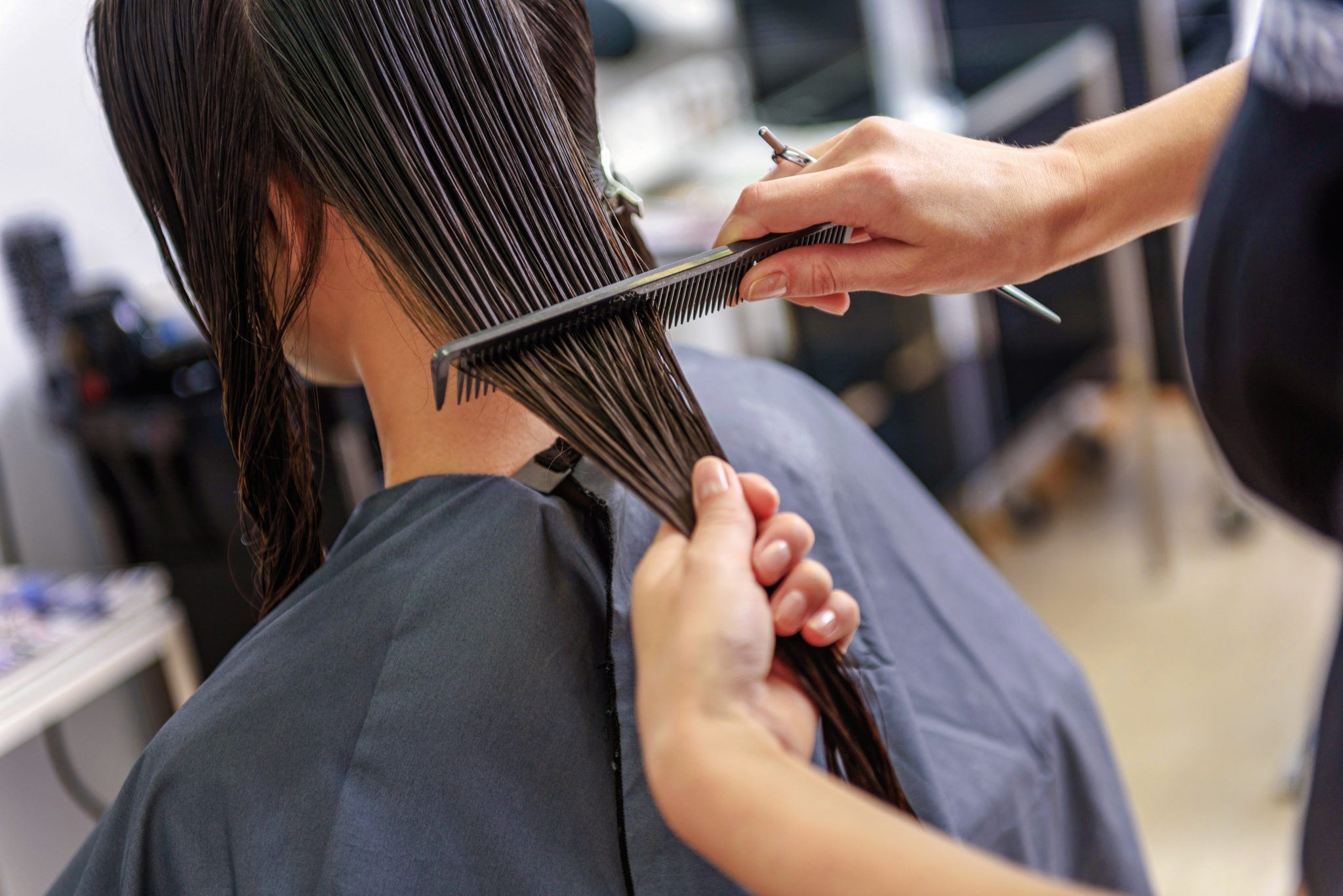 close up of hairdresser combing wet hair of a woman